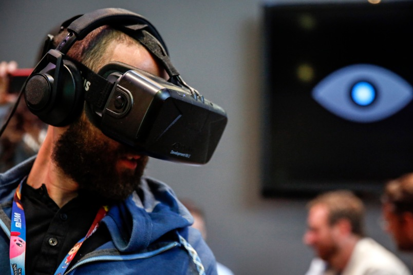An attendee wears an Oculus VR Inc. Rift Development Kit 2 headset to play a video game during the E3 Electronic Entertainment Expo in Los Angeles on  June 11.